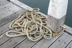 Wooden pier with bollard and long rope Stock Image