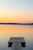 Wooden pier in the calm evening lake portrait Royalty Free Stock Photo