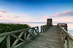 Wooden pier on calm lake at sunset Stock Image