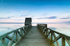 Wooden pier on calm lake at sunset Royalty Free Stock Photography