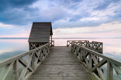 Wooden pier on calm lake at sunset Stock Images