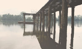 Wooden pier with chairs on foggy Drina lake, Serbia Royalty Free Stock Images