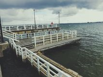 Wooden pier on cloudy day. Broken wooden pier on cloudy day. Horizontal view stock images