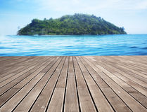 Wooden pier and distant tropical island in the background Royalty Free Stock Photo