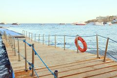 Wooden pier of Dive Station. Life belt. Yachts on the horizon. stock photography