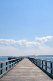 Wooden pier extending into ocean, hazy blue sky Stock Image