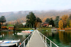 A wooden pier extends into a crystal clear alpine lake in Autumn, France Royalty Free Stock Photo