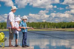 On a wooden pier the father teaches his sons to fish. Properly Royalty Free Stock Photo