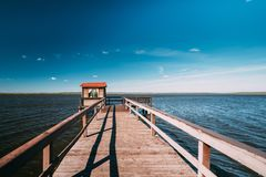 Wooden Pier For Fishing, Small House Shed And Beautiful Lake Or. Old Wooden Pier For Fishing, Small House Shed And Beautiful Lake Or River In Background stock photography
