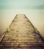 Wooden pier in fog. Wooden pier stretching out over foggy lake or river stock image