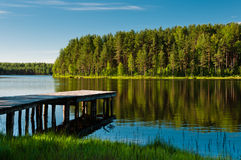 Wooden pier and forest on lake Royalty Free Stock Photos