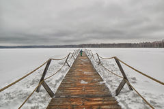 Wooden pier on a frozen winter lake Royalty Free Stock Images