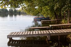 Wooden pier on the lake side view with green trees. summer day stock photos