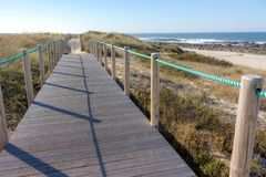 Wooden pier with grass on Atlantic ocean coast, Portugal. Wooden boardwalk to sea on rocks shore. Empty walkway in dunes at dawn. stock image