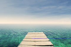 Wooden pier on a green ocean Royalty Free Stock Images