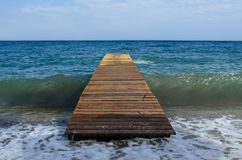 Wooden pier on the infinite sea without anyone under it passes a wave that breaks on the shore. Wooden pier on the infinite sea without anyone, under it passes a stock photography