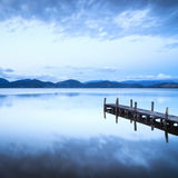 Wooden pier or jetty and on a blue lake sunset and sky reflectio Stock Images