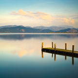 Wooden pier or jetty and on a blue lake sunset and sky reflection on water. Versilia Tuscany, Italy royalty free stock image