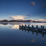 Wooden pier or jetty on a blue lake sunset and sky reflection on Royalty Free Stock Photos