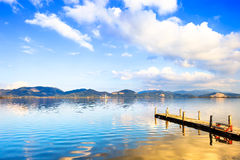 Wooden pier or jetty and on a blue lake sunset and sky reflection on water. Versilia Tuscany, Italy. Wooden pier or jetty and on a blue lake sunset and cloudy Stock Photo