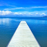 Wooden pier or jetty on a blue ocean. Beach in Argentario, Tuscany, Italy Stock Image