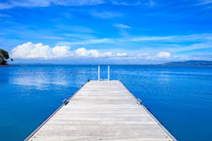 Wooden pier or jetty on a blue ocean. Beach in Argentario, Tuscany, Italy. Wooden pier or jetty on a blue ocean and clear sky. Bay beach in Monte Argentario Stock Photos