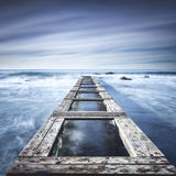 Wooden pier or jetty on a blue ocean. Long Exposure Royalty Free Stock Image