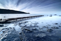 Wooden pier or jetty on a blue ocean in the morning. Long Exposu Royalty Free Stock Photos