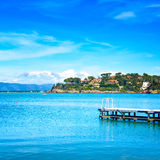 Wooden pier or jetty on a blue sea. Beach in Argentario, Tuscany, Italy Royalty Free Stock Image
