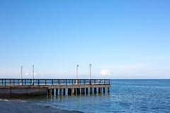Wooden pier or jetty on a blue sea and sky background Royalty Free Stock Photography
