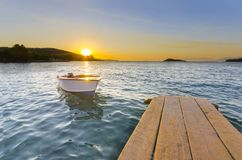 Wooden pier or jetty and a boat on a lake sunset stock image