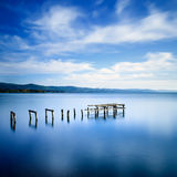 Wooden pier or jetty remains on a blue lake. Long Exposure. Royalty Free Stock Image