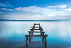 Wooden pier or jetty remains on a blue lake. Long Exposure. Wooden pier or jetty remains on a blue lake sunset. Long Exposure photography Royalty Free Stock Photos