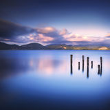 Wooden pier or jetty remains on a blue lake sunset and sky refle Royalty Free Stock Images