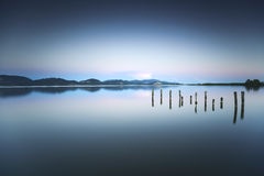 Wooden pier or jetty remains on a blue lake sunset and sky refle Stock Image