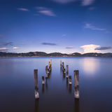 Wooden pier or jetty remains on a blue lake sunset and sky refle Royalty Free Stock Photo