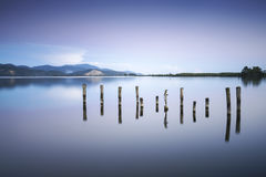 Wooden pier or jetty remains on a blue lake sunset and sky refle Stock Photo