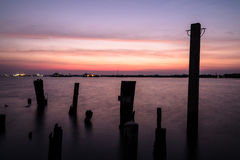 Wooden pier or jetty remains on blue lake sunset and sky reflection water Stock Photography