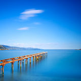 Wooden pier or jetty remains on a blue ocean lake. Long Exposure Royalty Free Stock Photos