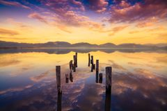 Wooden pier or jetty remains on a warm lake sunset and sky refle Royalty Free Stock Photos