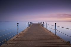 Wooden pier or jetty on sea sunset and sky reflection water. Long exposure, Dahab, Egypt.  Royalty Free Stock Photo