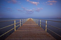 Wooden pier or jetty on sea sunset and sky reflection water. Long exposure, Sharm-el-Sheikh, Egypt Stock Image