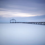 Wooden pier or jetty silhouette and blue ocean on sunset Stock Images