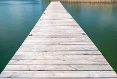 Wooden pier jutting out into a turquoise and blue lake with golden reeds in the background. A wooden pier jutting out into a turquoise and blue lake with golden Royalty Free Stock Photo