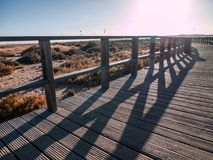 Wooden pier with kite surfers and beach in the background royalty free stock image