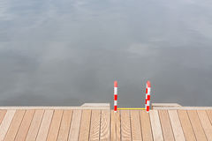 Wooden pier and ladder by the water Stock Photography