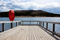 Wooden pier on a lake. Wooden pier of picturesque Icelandic lake with mountains in background Royalty Free Stock Photo