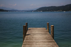 Wooden pier on lake. Scenic view of wooden pier on lake with mountains in background Stock Images