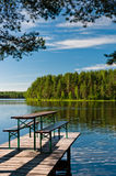 Wooden pier on lake with benches. Beautiful nature view Royalty Free Stock Image