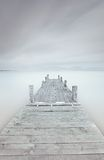 Wooden pier on lake in a cloudy and foggy mood. Stock Photo